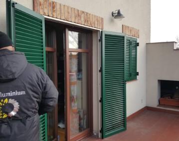 Okiennice aluminiowe zielone z ramą pracownik montuje