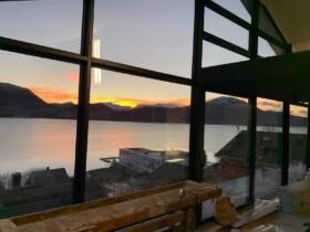 zachodzące słońce przez okna z dużymi szybami i wyjściem na taras